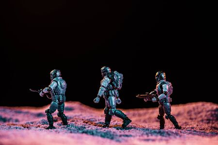 toy soldiers walking with gun on planet in space isolated on black