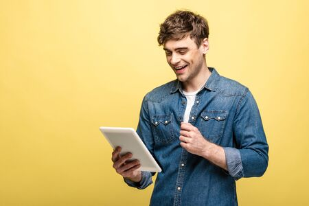 cheerful young man in denim shirt using digital tablet on yellow background