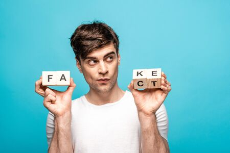 thoughtful man looking away while holding wooden cubes with fake fact lettering on blue background