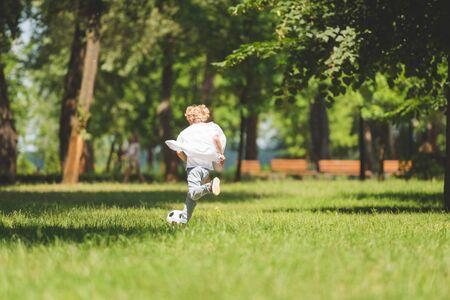 widok z tyłu chłopca grającego w piłkę nożną w parku w ciągu dnia