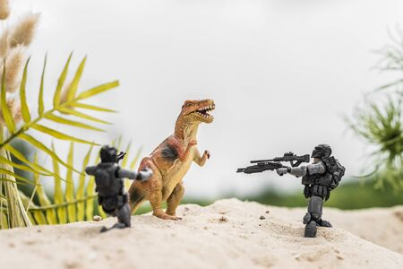 toy soldiers aiming with guns at toy dinosaur on sand hill
