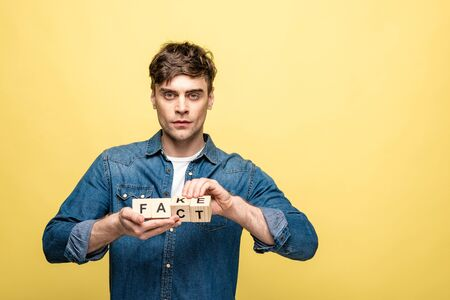 serious young man holding wooden cubes with fake fact lettering on yellow background
