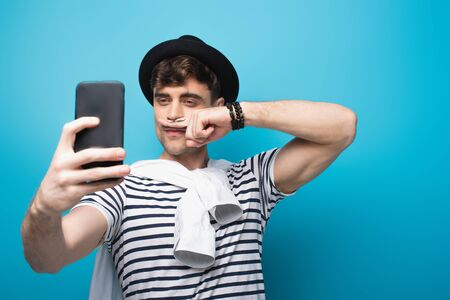 cheerful man taking selfie with smartphone while holding finger with drawn mustache near face on blue background