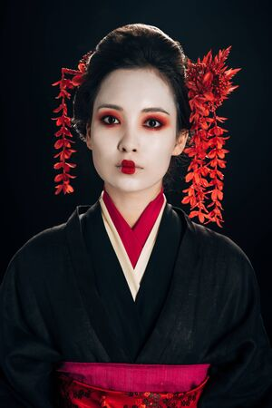 beautiful geisha in black and red kimono and flowers in hair isolated on black