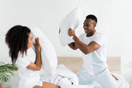 african american couple fighting on bed with pillows in hands