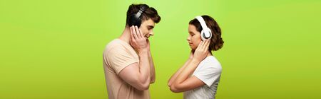 panoramic shot of positive man and woman in headphones listening music with closed eyes on green background Banque d'images
