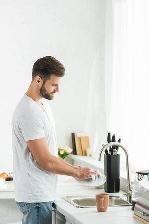 Gut aussehender Mann, der morgens in der Küche Geschirr wäscht