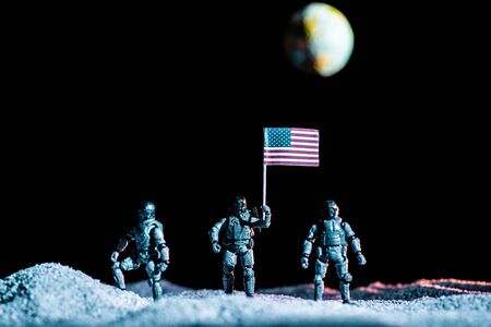 toy soldiers standing with usa flag on planet in space on black background with planet Earth