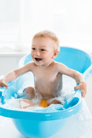 happy toddler kid smiling while taking bath in blue baby bathtub