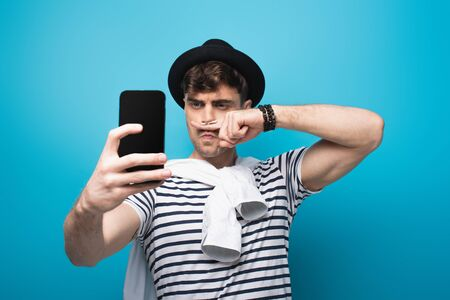 tricky man taking selfie with smartphone while holding finger with drawn mustache near face on blue background Stock Photo