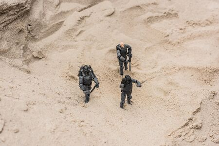 plastic toy soldiers on sand dune with guns Stock Photo