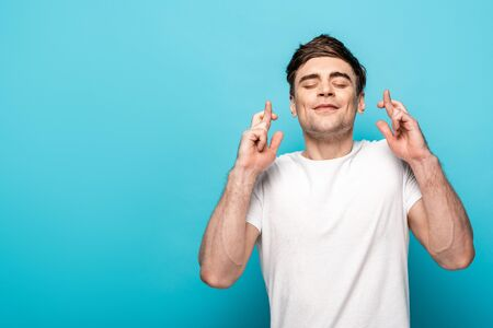 positive young man holding crossed fingers with closed eyes on blue background Banque d'images - 128058446