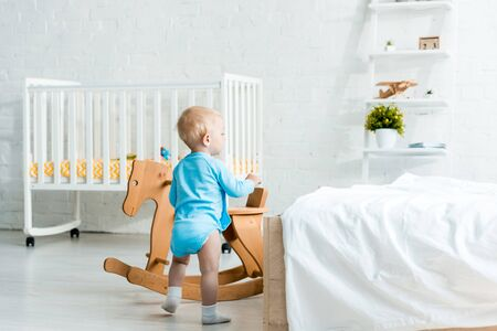 cute toddler child standing near wooden rocking horse in modern bedroom