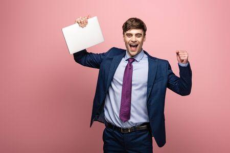 uomo d'affari felice che sorride alla macchina fotografica mentre tiene il laptop e mostra il gesto del vincitore su sfondo rosa