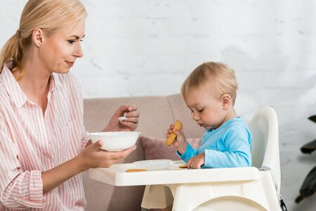 happy mother holding spoon with baby food near cute toddler son sitting in feeding chair Banco de Imagens