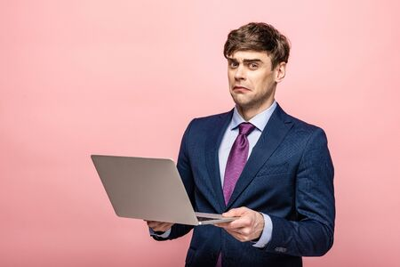 disappointed businessman looking at camera while holding laptop on pink background
