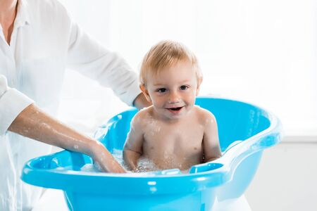 cropped view of mother washing happy toddler child in blue baby bathtub