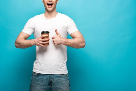 cropped view of smiling man holding coffee to go and showing thumb up on blue background