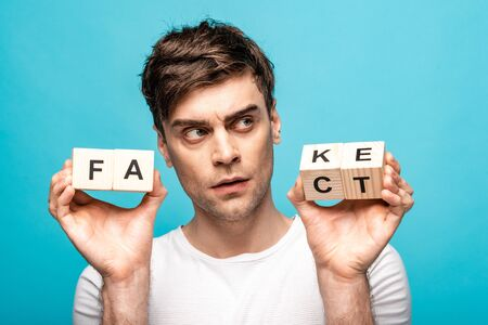 thoughtful young man looking away while holding wooden cubes with fake fact lettering isolated on blue