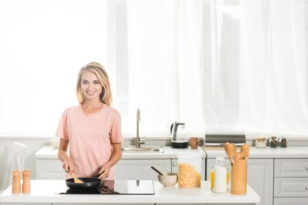 beautiful woman cooking with frying pan and spatula at kitchen in morning