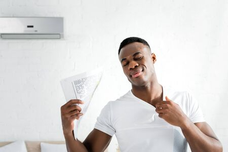 sweaty african american man closing eyes, standing in white room with heat temperature, holding newspaper in hand