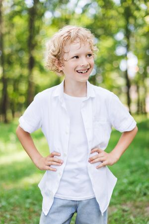 cute happy boy with Hands On Hips in park looking away Stock Photo