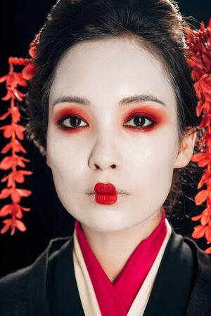 portrait of beautiful geisha with red eyeshadow and lips isolated on black