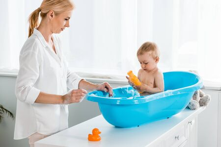 blonde mother looking at toddler son holding bottle with shampoo