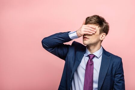 upset businessman covering eyes with hand on pink background