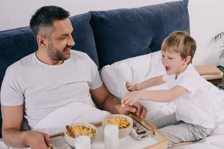 cheerful father and son having breakfast in while staying in bed together