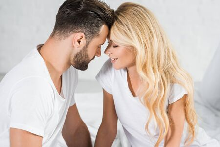 beautiful couple in white t-shirts touching with foreheads at home