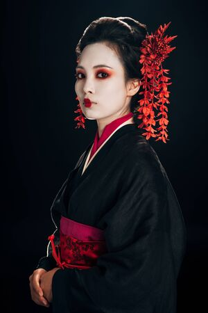 geisha in black and red kimono and flowers in hair isolated on black