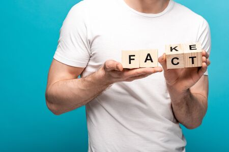 partial view of man holding wooden cubes with fake fact lettering on blue background