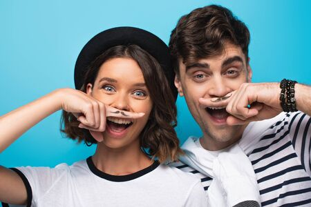 cheerful man and woman holding fingers with drawn mustache near faces on blue background Stock Photo