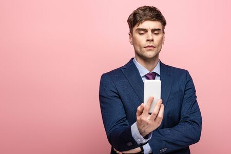 serious businessman in suit looking at smartphone isolated on pink Foto de archivo