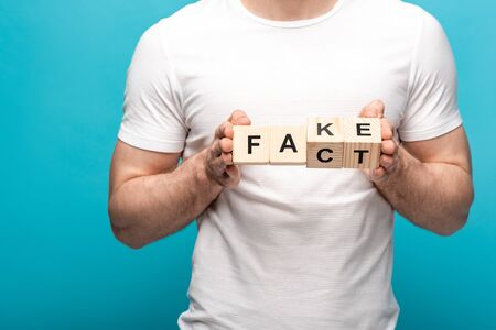 partial view of man in white t-shirt holding wooden cubes with fake fact lettering on blue background Stock Photo