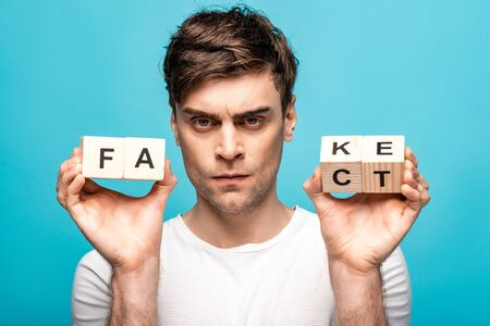 angry man showing wooden cubes with fake fact lettering and looking at camera isolated on blue