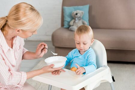 blonde mother holding bowl and feeding toddler son at home Banco de Imagens