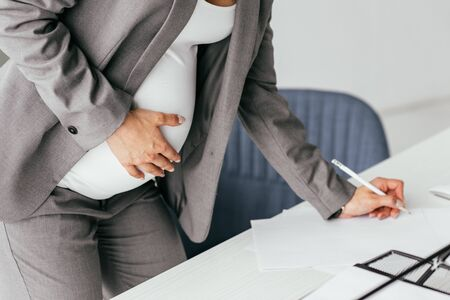 cropped view of pregnant woman in suit holding belly and making notes in notebook