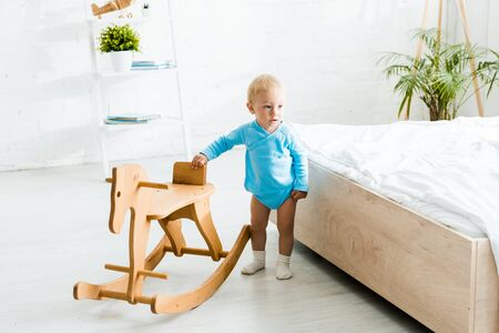 adorable toddler kid standing near wooden rocking horse in modern bedroom