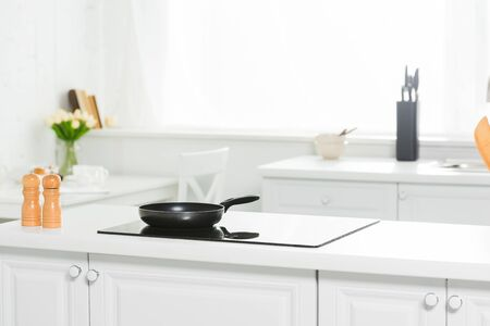 modern kitchen with white counter, cooker and frying pan