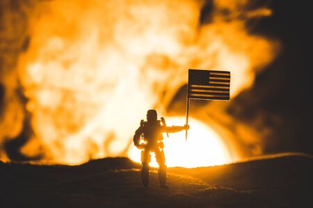 toy soldier silhouette with american flag on planet with sun in smoke