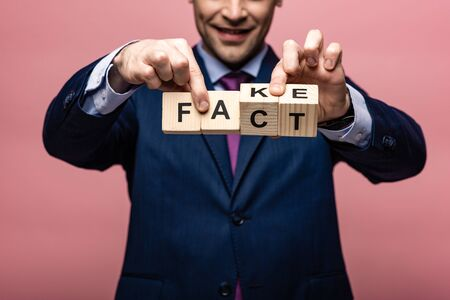 partial view of businessman holding wooden cubes with fake fact lettering on pink background Stok Fotoğraf
