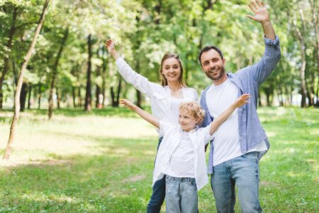 excited family with outstretched hands looking at camera in park 免版税图像