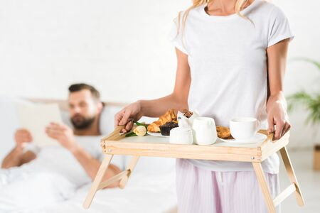 cropped view of woman holding food tray with breakfast in bedroom