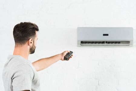 side view of man suffering from heat and switching temperature of air conditioner at home
