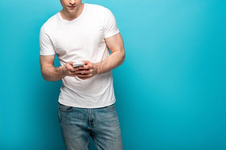 cropped view of young man in white t-shirt and blue jeans using smartphone on blue background