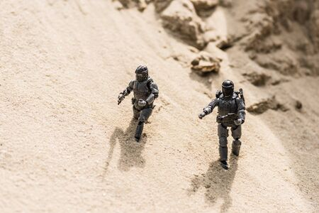 tiny toy soldiers on sand with shadows in daylight Stock Photo