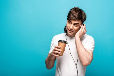 cheerful young man in headphones holding coffee to go and looking away on blue background