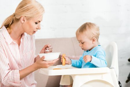attractive mother holding spoon with baby food near cute toddler son sitting in feeding chair Banco de Imagens